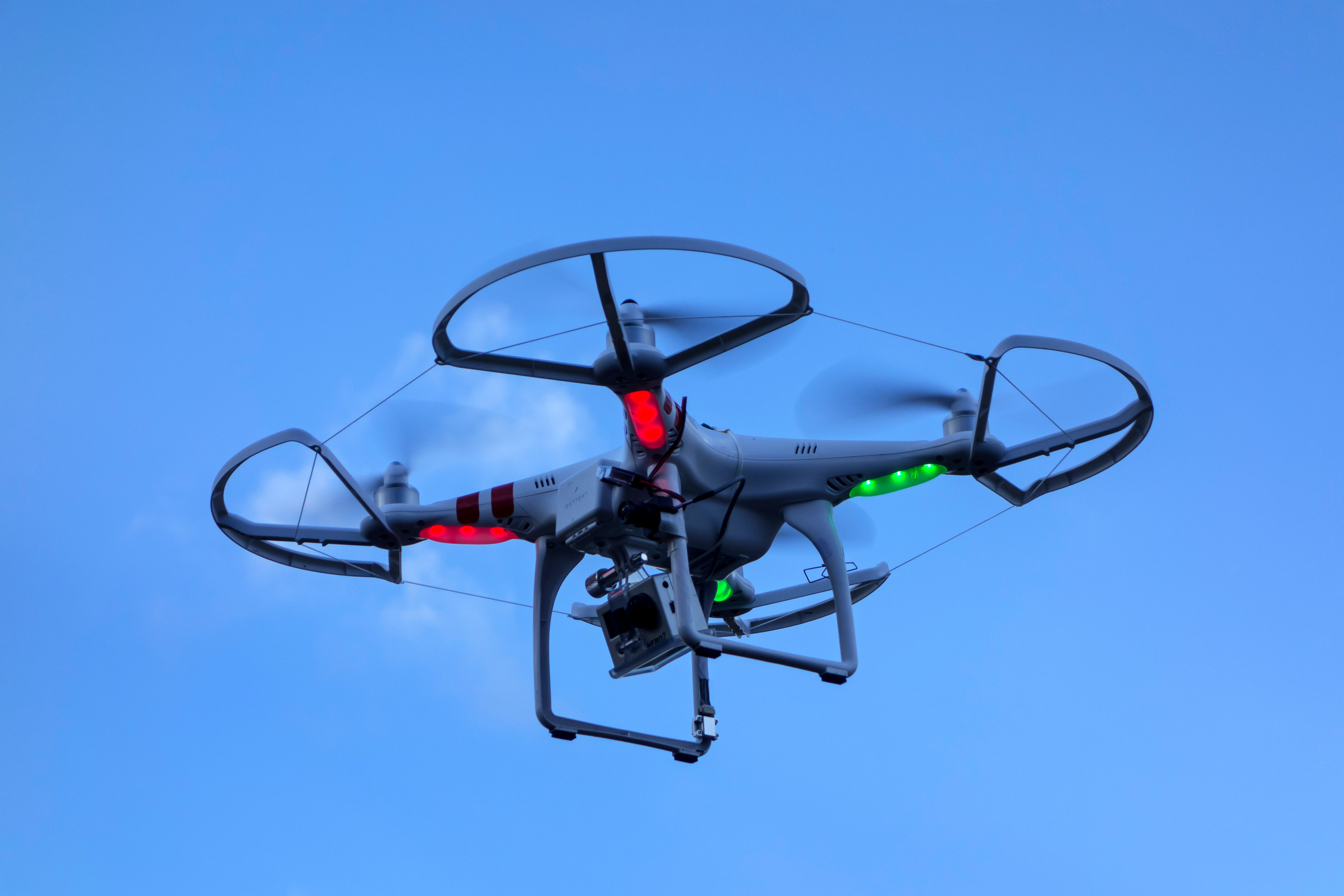 Miniature drone / unmanned aerial vehicle / UAV equipped with camera in flight against blue sky with clouds