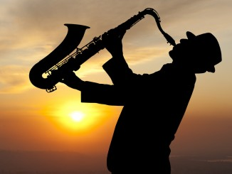 Saxophonist. Man playing on saxophone against the background of
